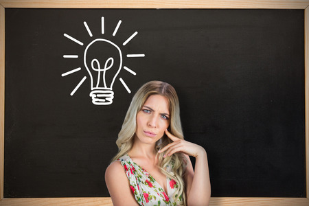 Frowning pretty blonde wearing flowered dress posing against chalkboard with wooden frame photo