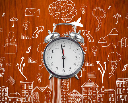 Alarm clock against wooden oak table with doodles photo