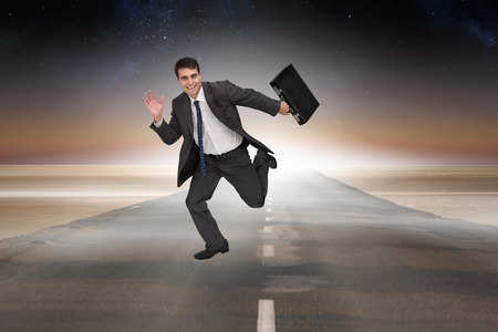 Cheerful businessman in a hurry against road leading out to the horizon photo