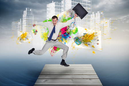 Cheerful jumping businessman with his suitcase against holographic cityscape in sky photo