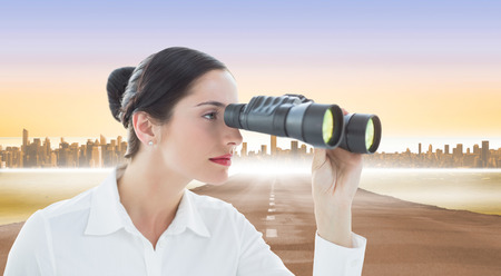 Business woman looking through binoculars against cityscape on the horizon photo