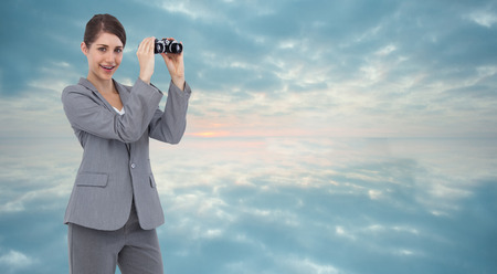 Businesswoman posing with binoculars against clouds reflected on water photo