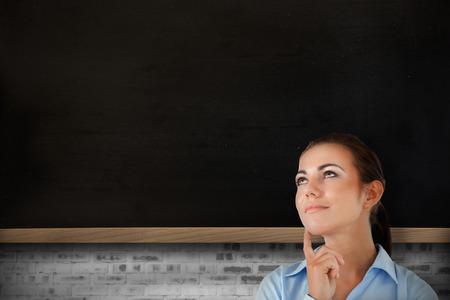 Thinking businesswoman looking upwards against chalkboard on grey brick wall photo