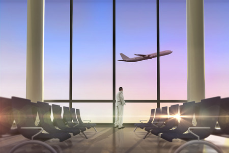 Thinking businessman against airplane flying past departures lounge photo