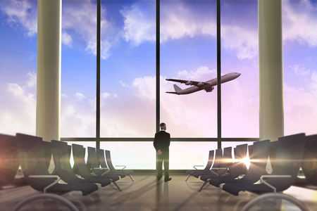 Rear view of mature businessman posing against airplane flying past departures lounge photo