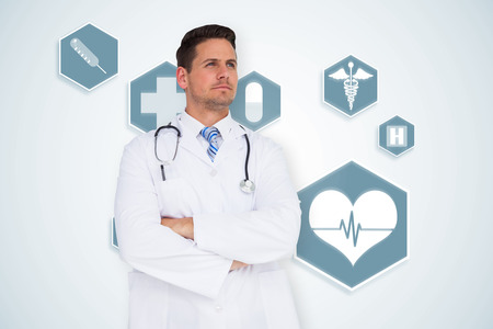 Handsome doctor with arms crossed against blue medical interface with icons photo