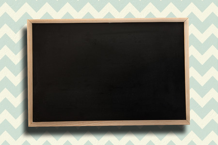 patterned wallpaper: Chalkboard with wooden frame against blue and cream patterned wallpaper Stock Photo