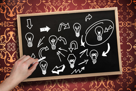 Composite image of hand drawing light bulbs with chalk on chalkboard with wooden frame photo