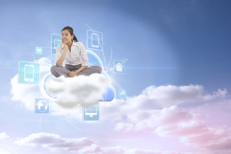 Businesswoman sitting cross legged thinking against beautiful blue cloudy sky photo