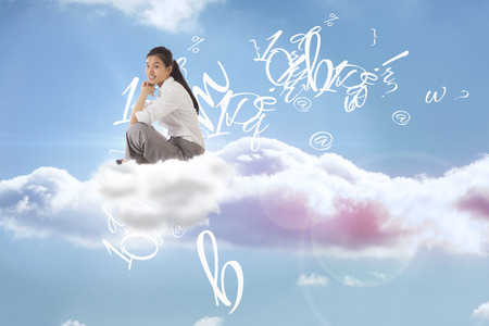 Businesswoman sitting cross legged with hands together against beautiful blue sky with clouds photo