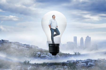 Thinking man in light bulb against rocky landscape photo