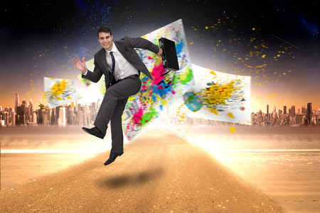 Smiling businessman in a hurry against large city on the horizon photo