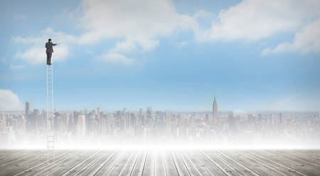 Businessman standing on ladder against cityscape on the horizon photo