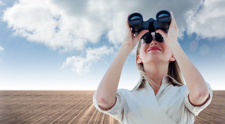 Businesswoman looking through binoculars against cloudy sky background photo