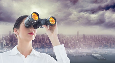 Business woman looking through binoculars against coastline and city photo