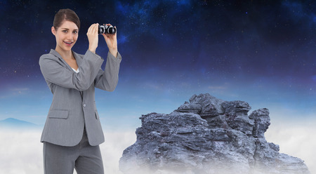 Businesswoman posing with binoculars against rocky landscape photo