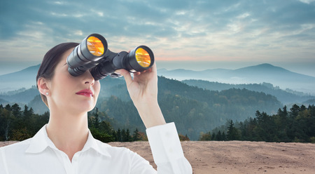 Business woman  looking through binoculars against scenic countryside with mountains photo