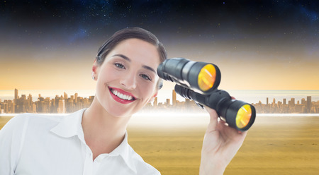 Smiling business woman with binoculars against cityscape on the horizon photo