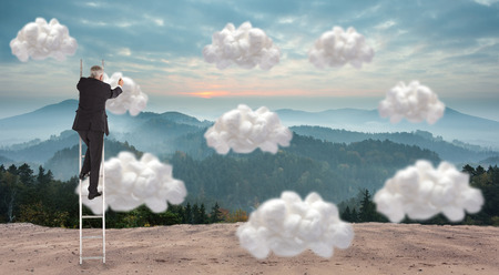 Mature businessman climbing career ladder against white cloud computing clouds photo