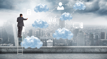 Businessman standing on ladder against cloud computing graphic with icons  photo