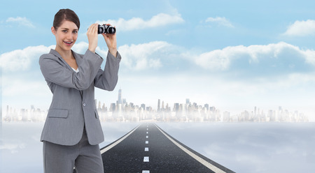 Businesswoman posing with binoculars against open road background photo