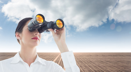 Business woman  looking through binoculars against cloudy sky background photo