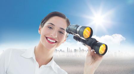 mujer mirando el horizonte: Sonriente mujer de negocios con binoculares contra el paisaje urbano en el horizonte Foto de archivo