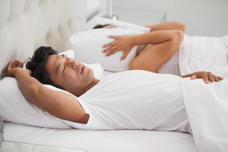 loudly: Woman covering her ears as partner is snoring loudly at home in bedroom Stock Photo