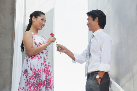 Man offering a red rose to girlfriend on the stairs photo