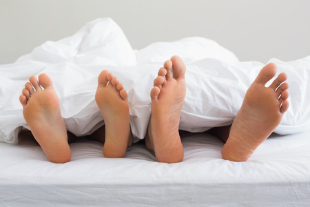 Couples feet sticking out from under duvet at home in bedroom photo