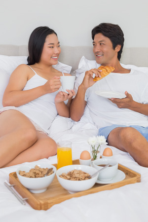 Happy couple having breakfast in bed at home in bedroom photo