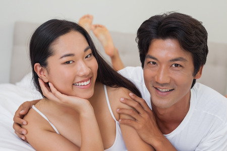Happy couple lying on bed embracing at home in bedroom photo