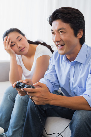Woman being ignored by boyfriend playing video games at home in the living room photo