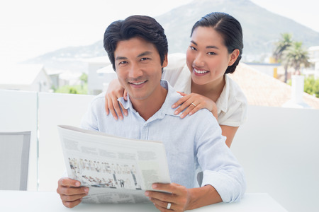 Couple reading a newspaper together outside on a balcony photo