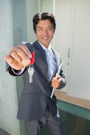 Confident estate agent standing at front door showing key outside a house photo