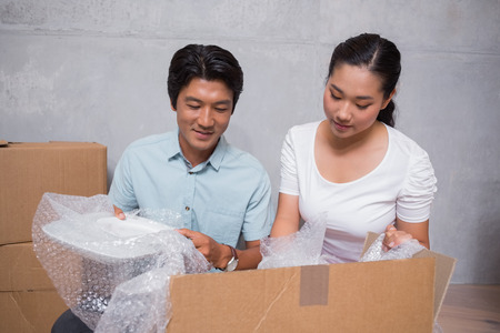 Happy couple sitting on floor unpacking boxes in their new home photo
