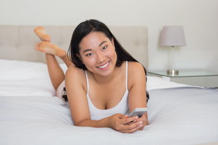 Happy woman lying on bed holding smartphone at home in bedroom photo