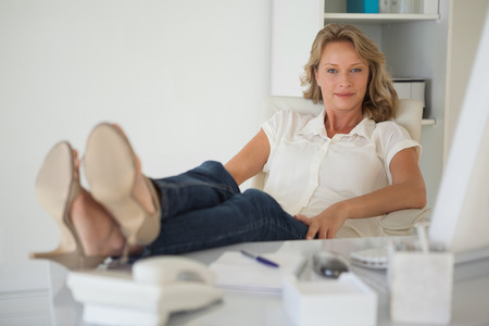 in her Casual businesswoman sitting at her desk with feet up office photo