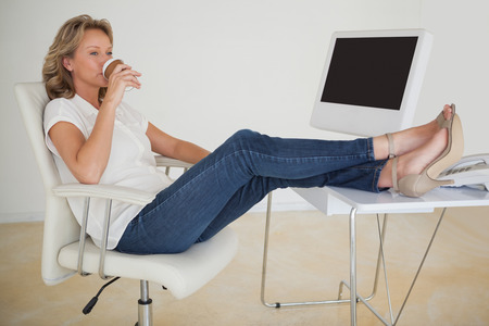 Casual businesswoman having a coffee with her feet up at desk in her office Stock Photo - 29009007