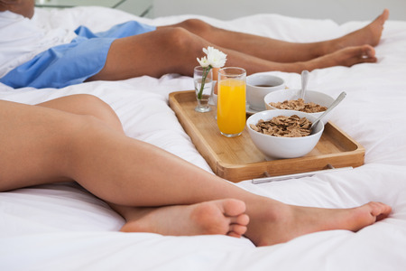 Couple lying on bed with breakfast on a tray at home in bedroom photo