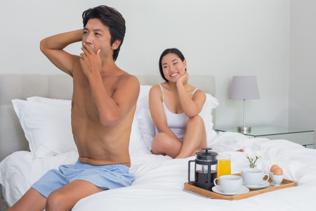 Smiling woman watching her boyfriend yawn and stretch at home in bedroom photo