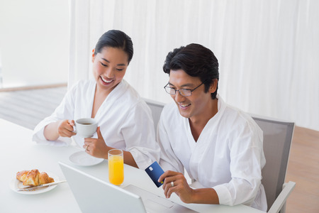 Couple in bathrobes shopping online in the morning at home in the living room photo