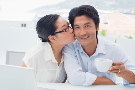 Woman kissing her boyfriend on the cheek having coffee outside on a balcony photo