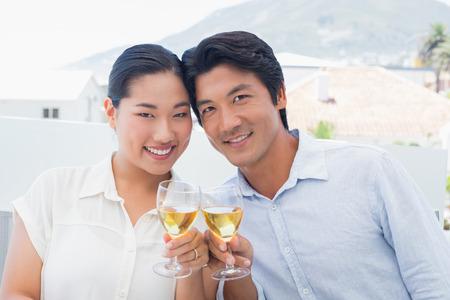 Happy couple having white wine outside on a balcony photo