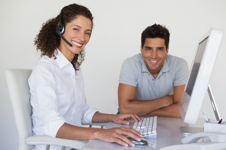 Casual business team smiling at camera together at desk in the office photo