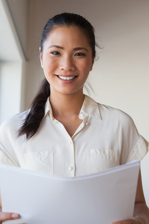 Casual businesswoman holding document and smiling at camera in the office photo