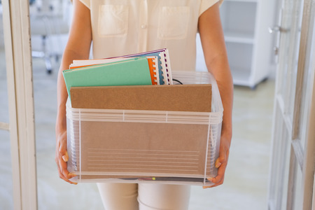 unemployed dismissed: Fired businesswoman holding box of her things in the office Stock Photo