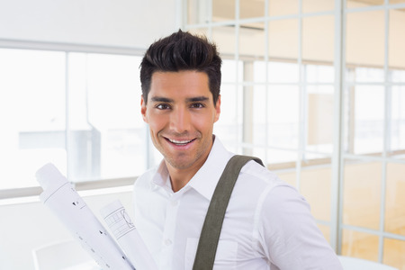 Casual handsome architect smiling at camera holding blueprint in the office photo