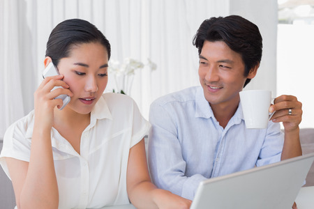 Couple using laptop with woman talking on phone at home in the living room photo