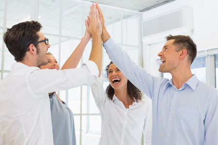 Casual business team high fiving in the office Stock Photo